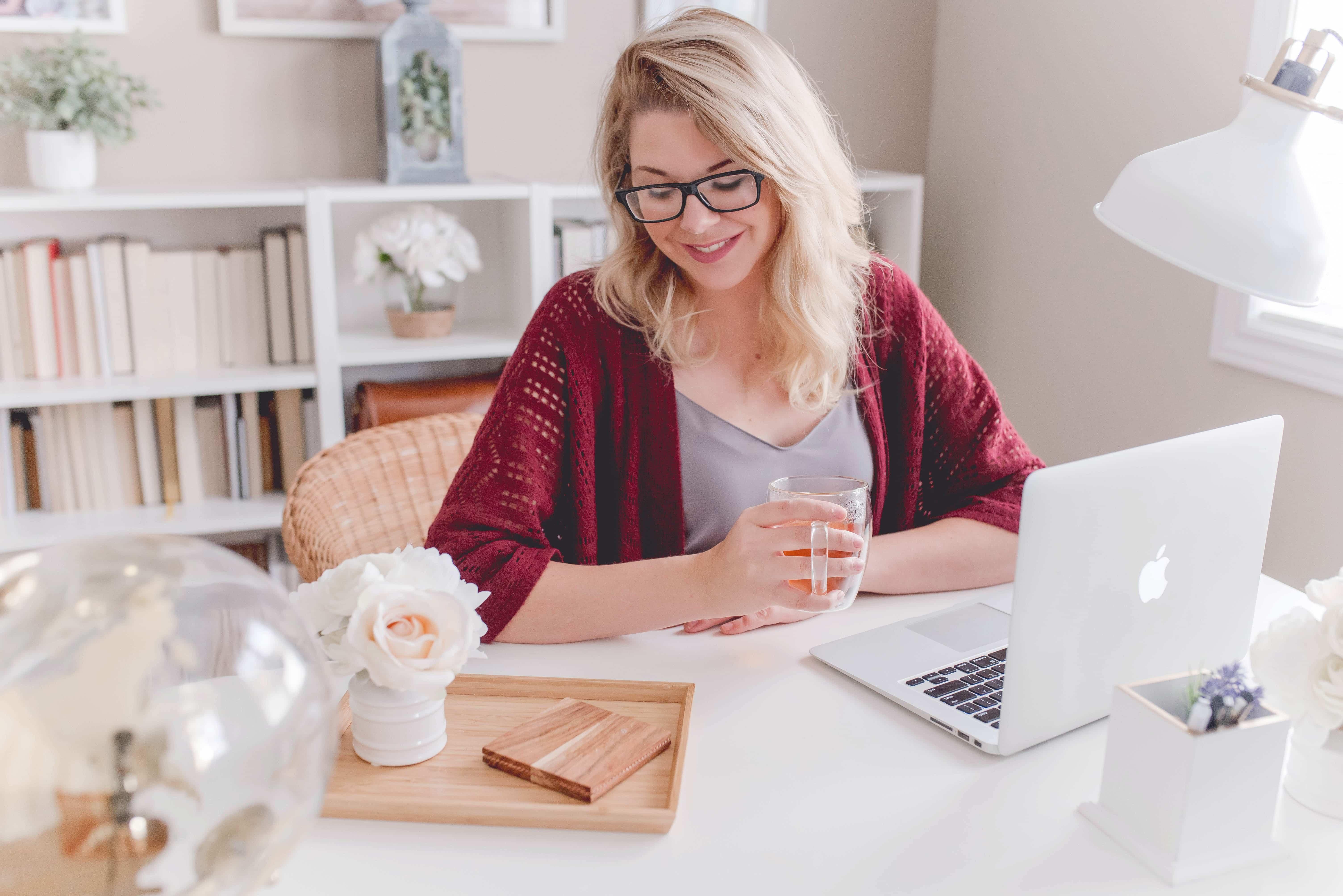 Vrouw schrijft vacature achter laptop.
